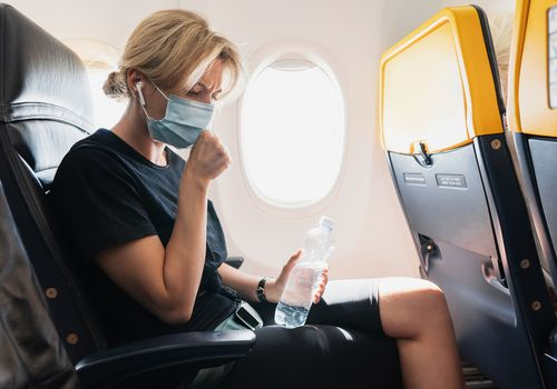 A blonde woman wearing a face mask on an airplane. Her hand is in front of her mouth like she's coughing and she's holding a water bottle.