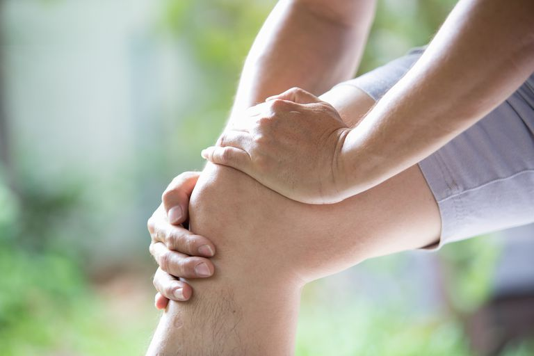 person experiencing Joint pain, holding their knee