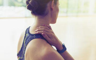 Woman rubbing neck at gym