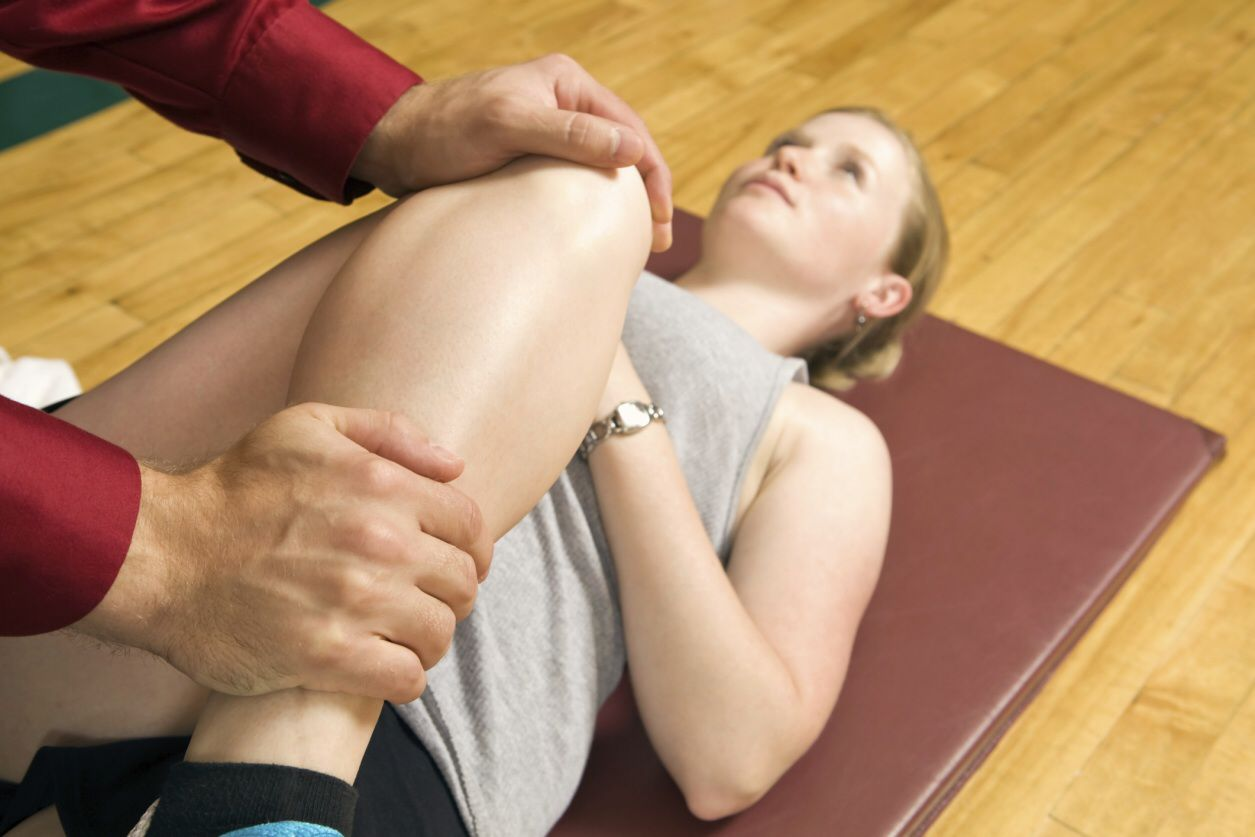 Physical therapist examining a woman's knee.