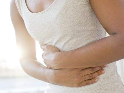 woman with abdominal pain holding stomach