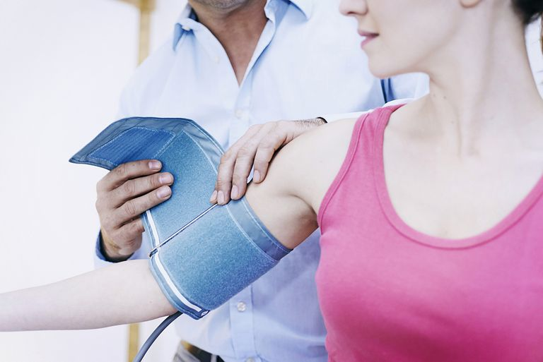 Doctor putting a blood pressure cuff on a woman