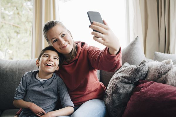 Smiling mother taking selfie with autistic son while sitting on sofa at home - stock photo
