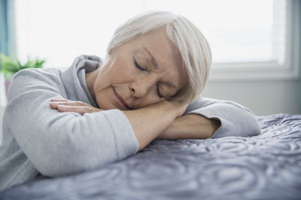 Tired woman laying on bed with eyes closed