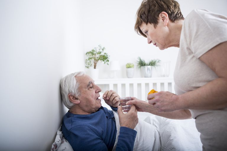 woman helping senior man take medication in bed