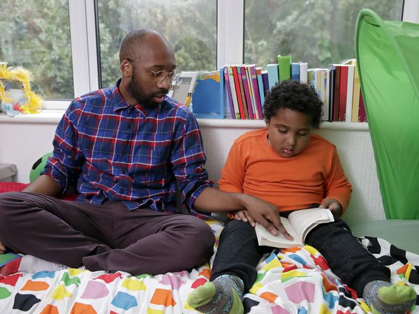 Father and son reading together on the floor