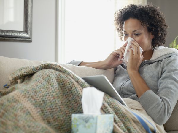 Woman with a cold looking at digital tablet