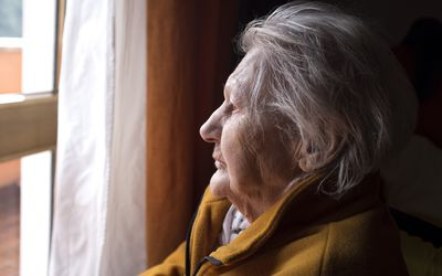 A woman with Alzheimer's looking out the window