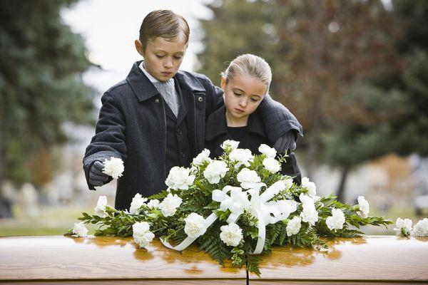 Children standing next to coffin