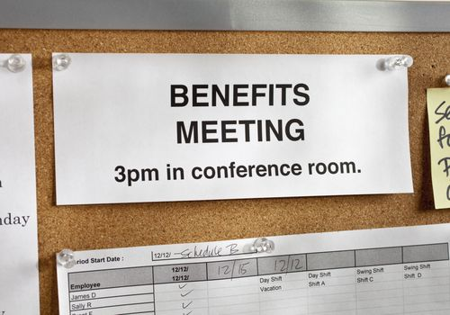 """benefits meeting"" sign on a corkboard"
