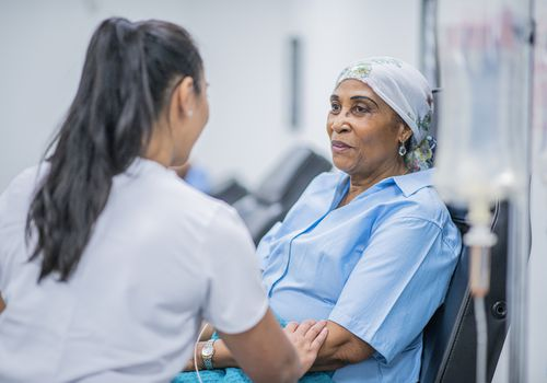 Older woman receiving cancer treatment.