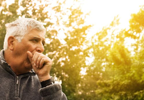 senior man coughing outside