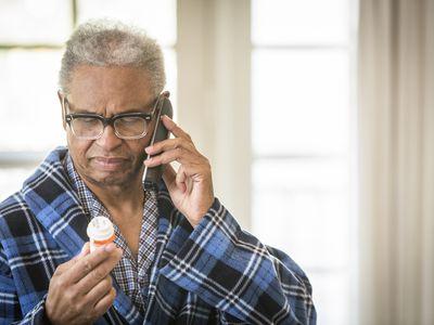 senior man on the phone reading his prescription bottle