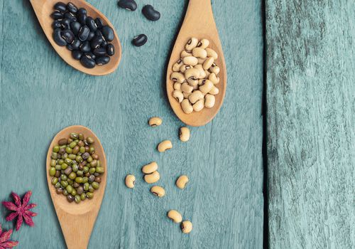 legumes in wooden spoons on a wooden table