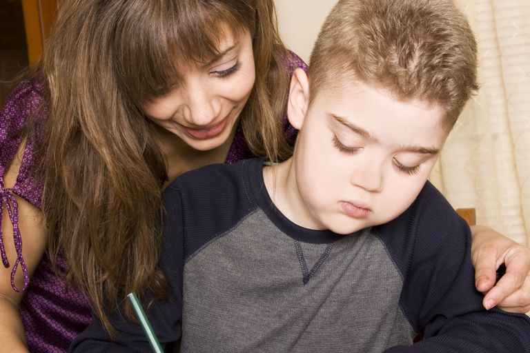 A mother helping her autistic son with his homework.