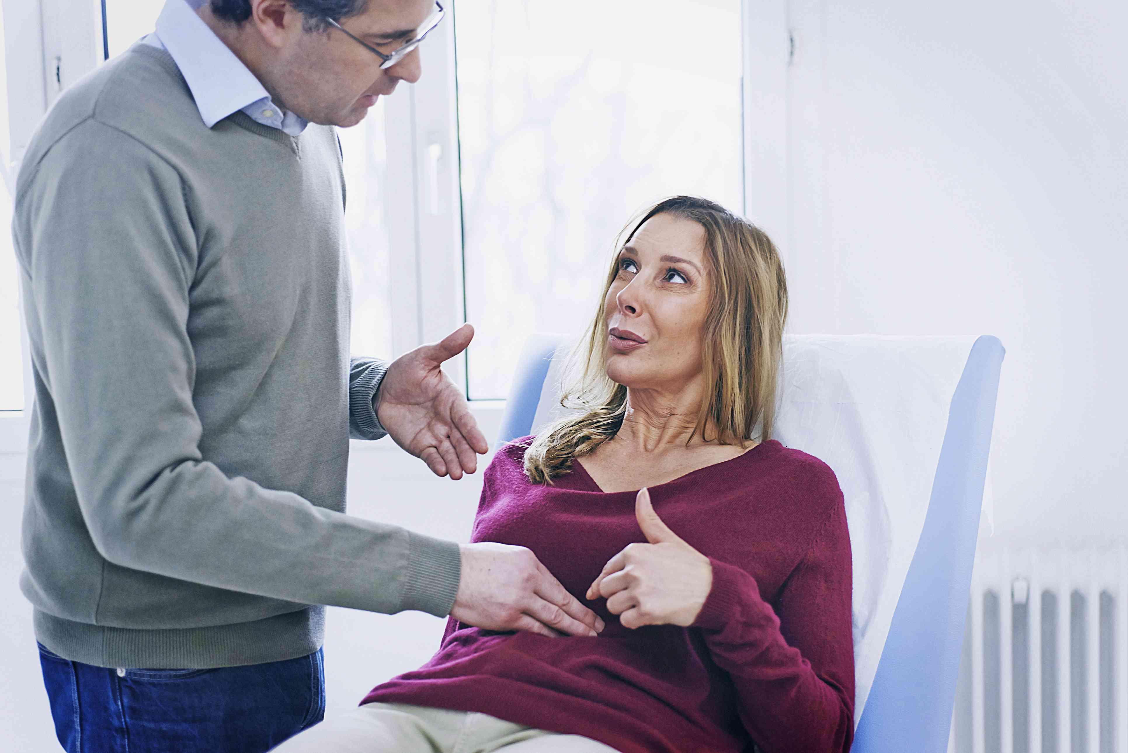 Doctor in casual clothes examining a patient's abdomen