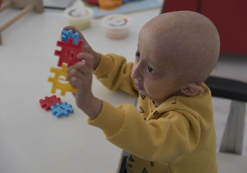 girl with progeria condition playing with puzzle