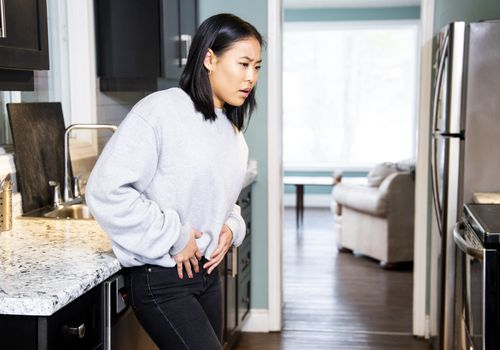 A women in the kitchen with pelvic pain