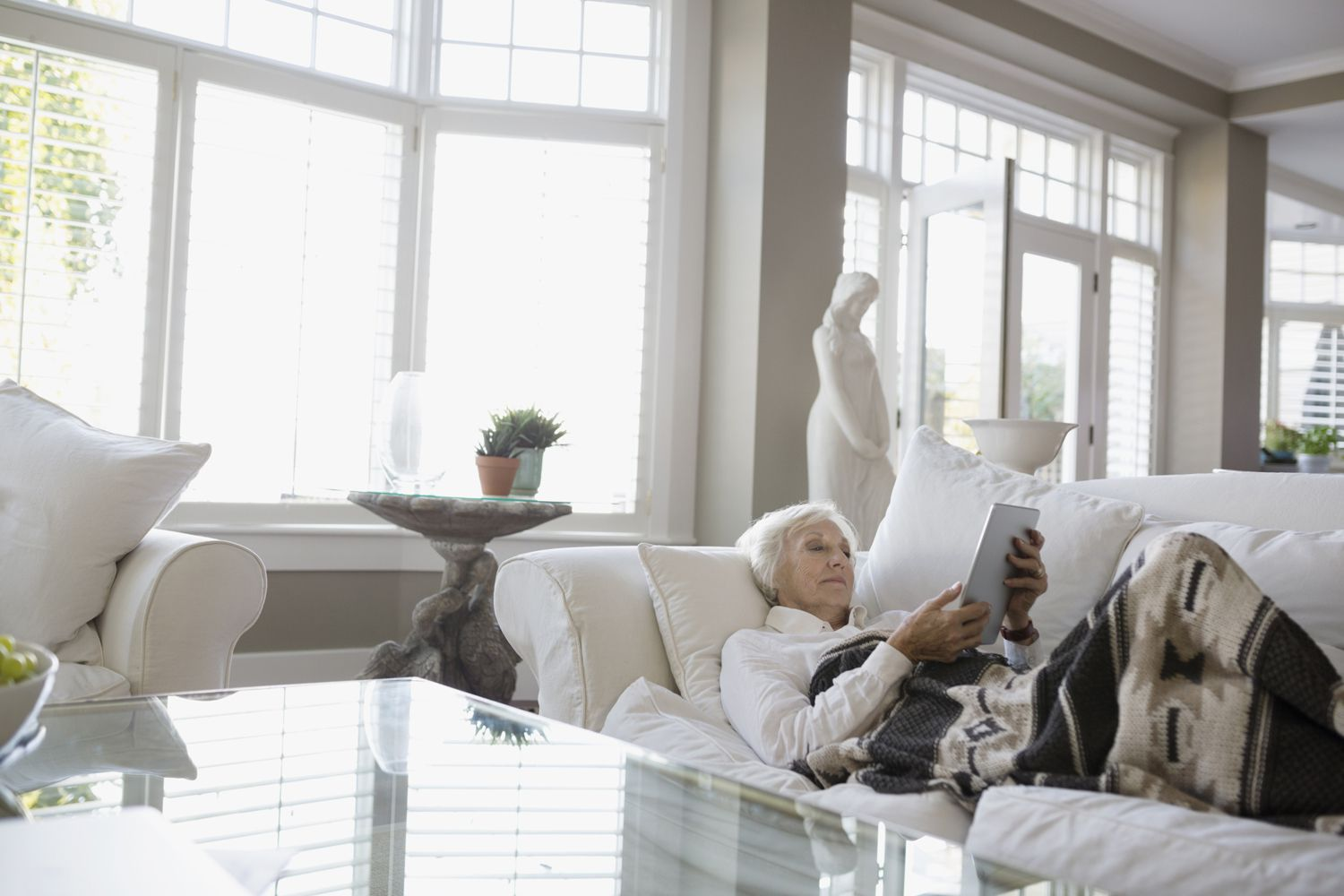 Older woman laying on a couch using a tablet