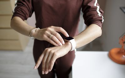 Woman tipping on smart watch at home