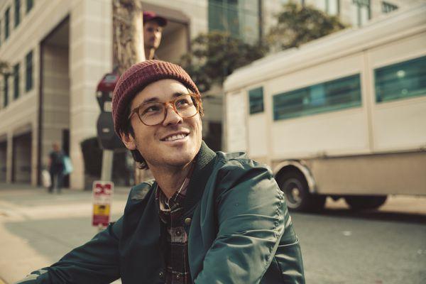 Portrait of stylish young man sitting on sidewalk