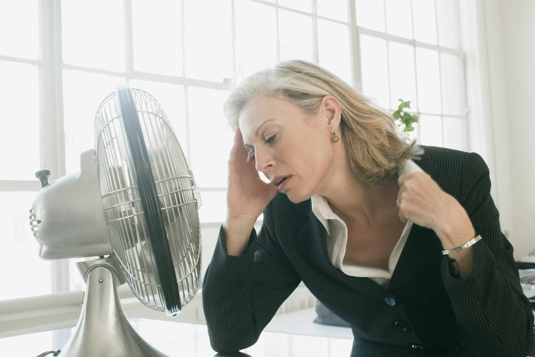 Businesswoman sitting in front of fan cooling off