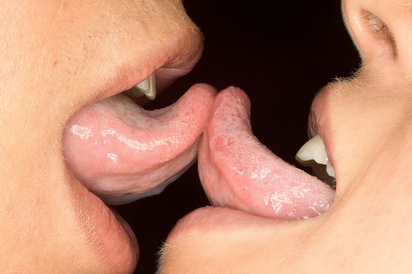Two people touching tongues