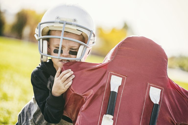Boy in a football helmet tackling a dummy