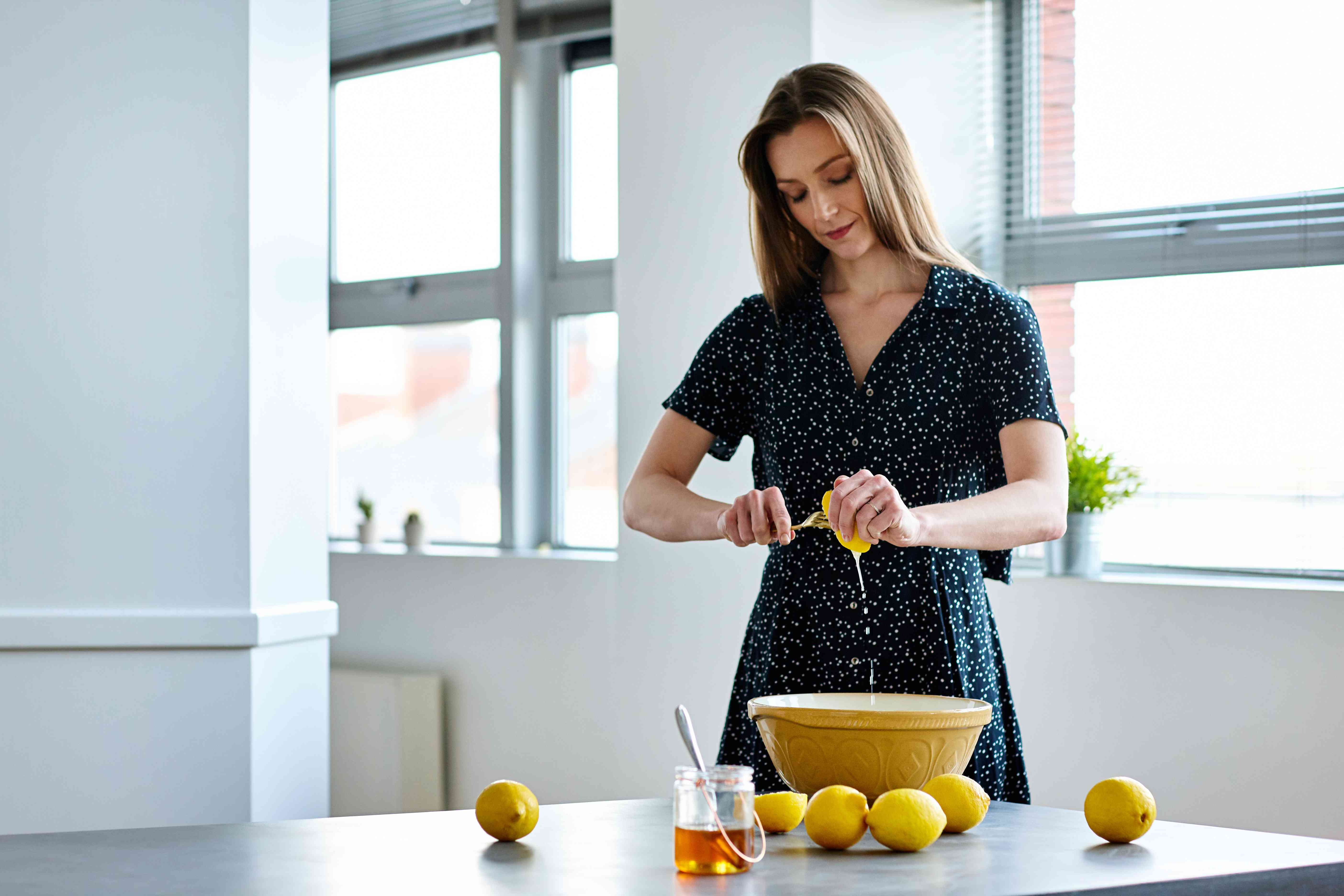 Beautiful mature woman preparing lemon juice at home