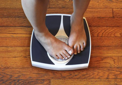 A woman's feet are on a bathroom scale and one foot is covering the weight reading.