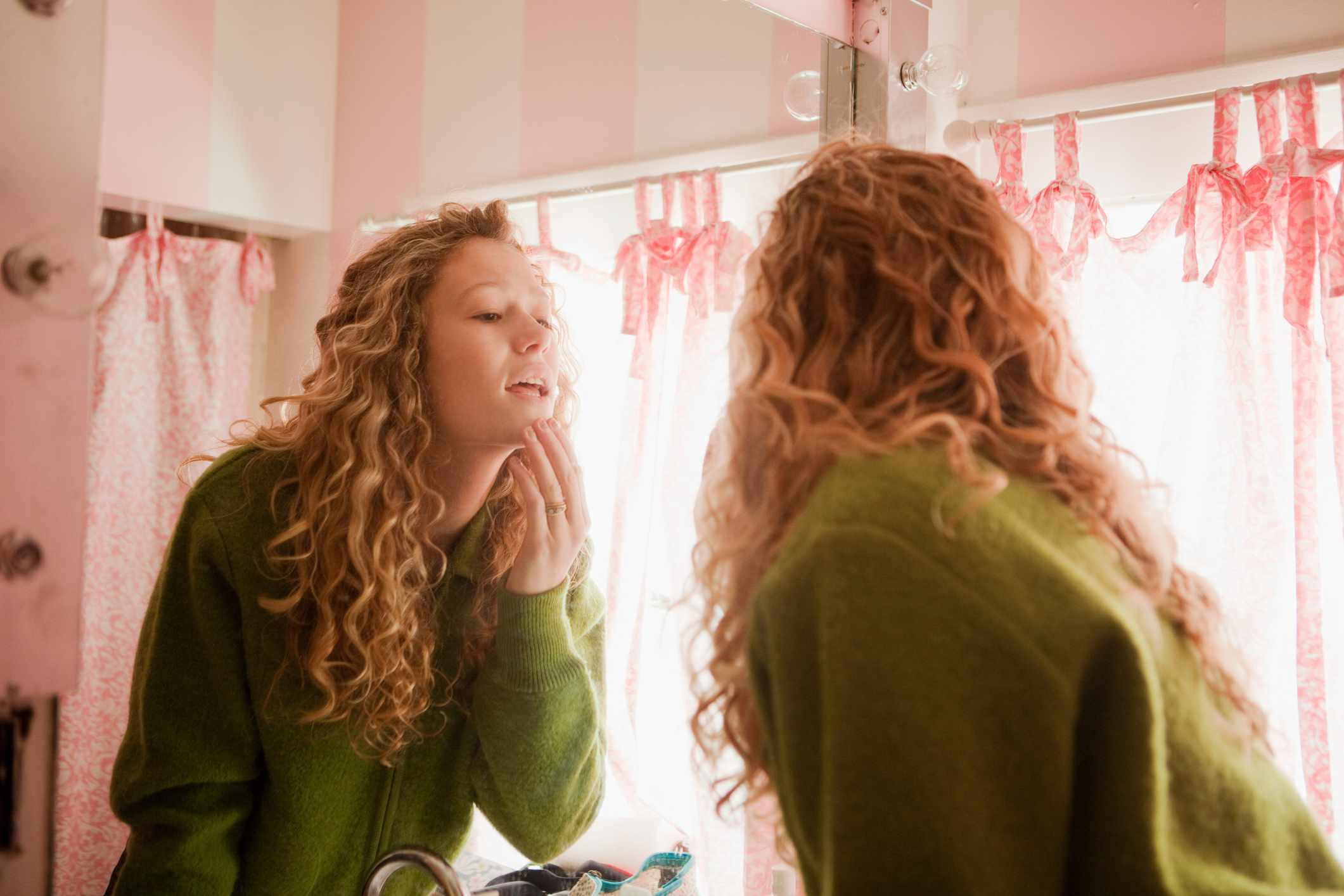 Young woman examining her skin in the bathroom mirror