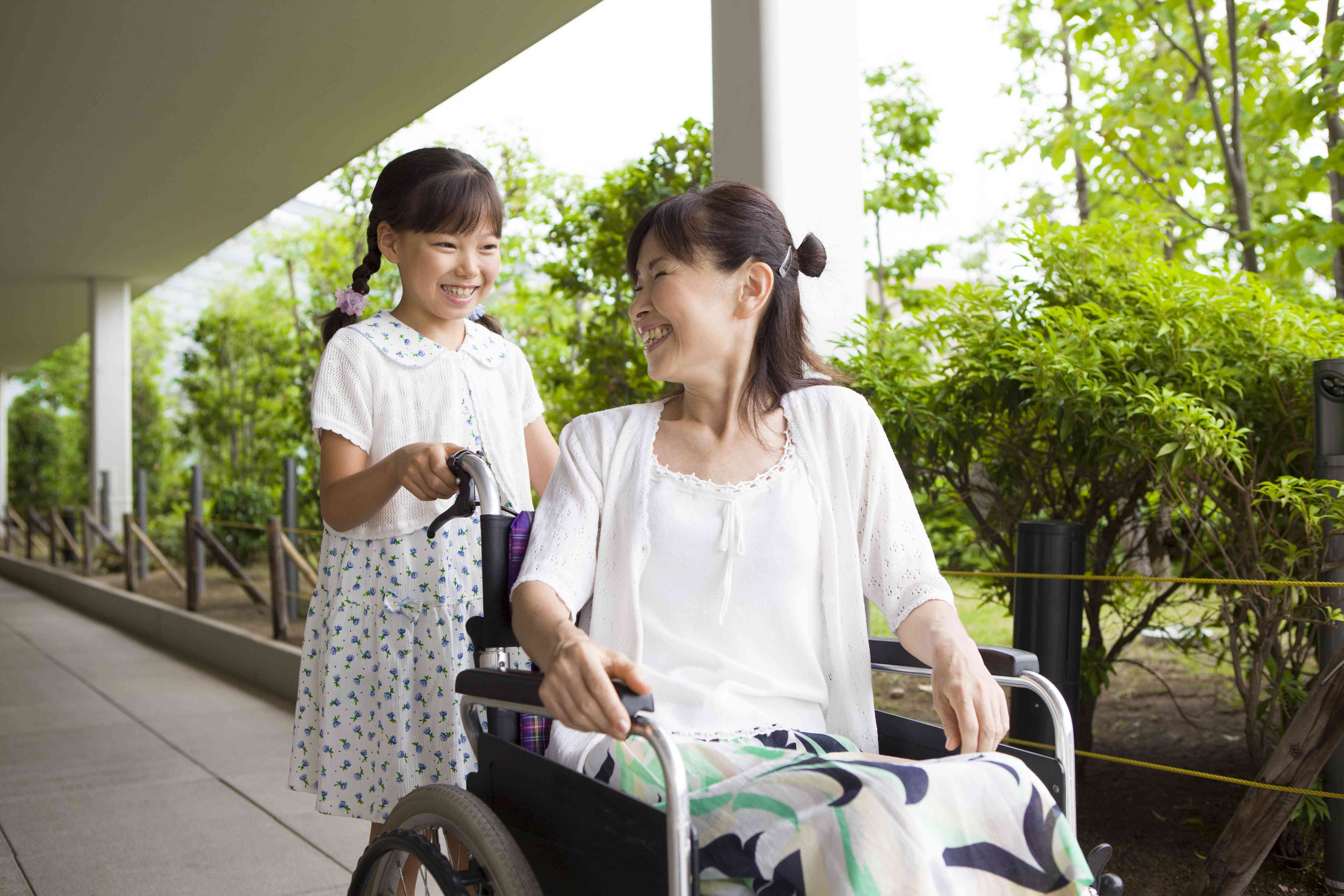 Child pushing adult in wheelchair