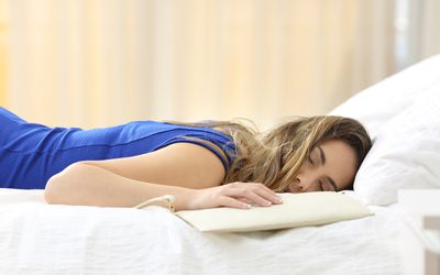 Woman asleep on bed during the day