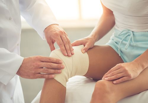 Knee bandage on woman at doctor