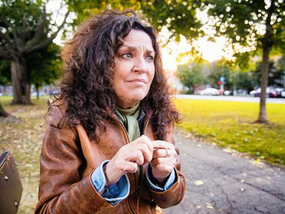 An anxious senior woman sitting outdoors on a park bench while rubbing her index finger.