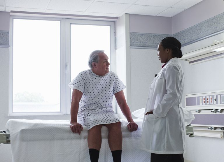 Man in a hospital gown consulting with his doctor