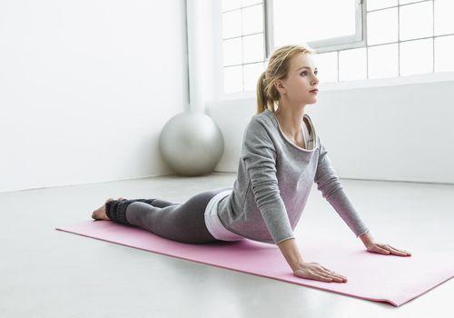 woman on a yoga mat doing upward facing dog pose