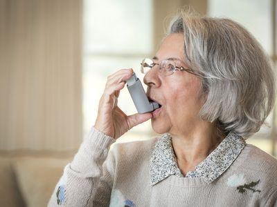 adult using asthma inhaler