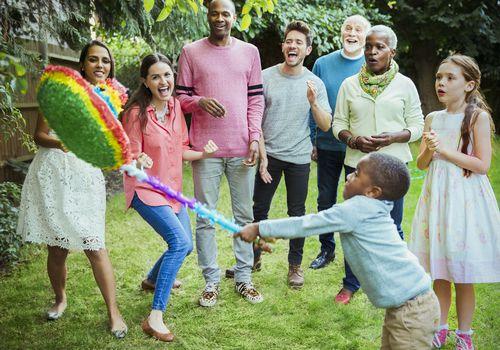 Multi-ethnic multi-generation family cheering boy hitting pinata at birthday party