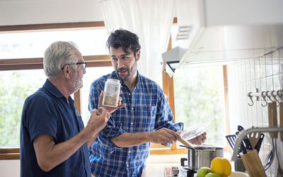 Adult son cooking with his older father in the kitchen