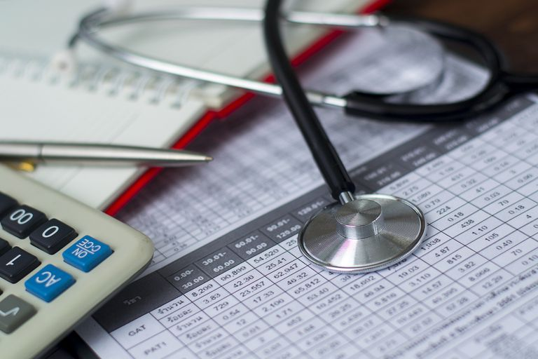 Medical bill under stethoscope and calculator