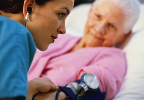 Nurse with stethoscope taking elderly patient's blood pressure