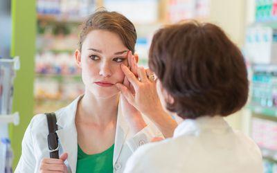 Pharmacist examining womans eye.
