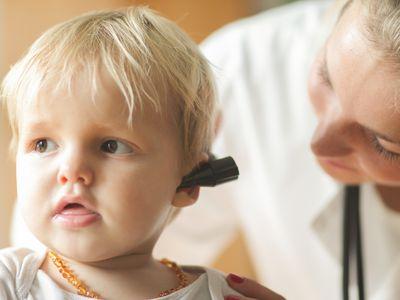 Female doctor looking into baby boy's ear