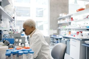 Lab technician examining sample under microscope