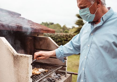 man grilling with face mask