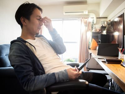 A man showing a tired expression while working from home