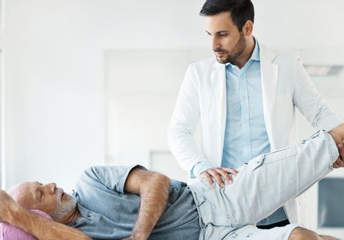 Doctor examining the hip of a patient during an appointment