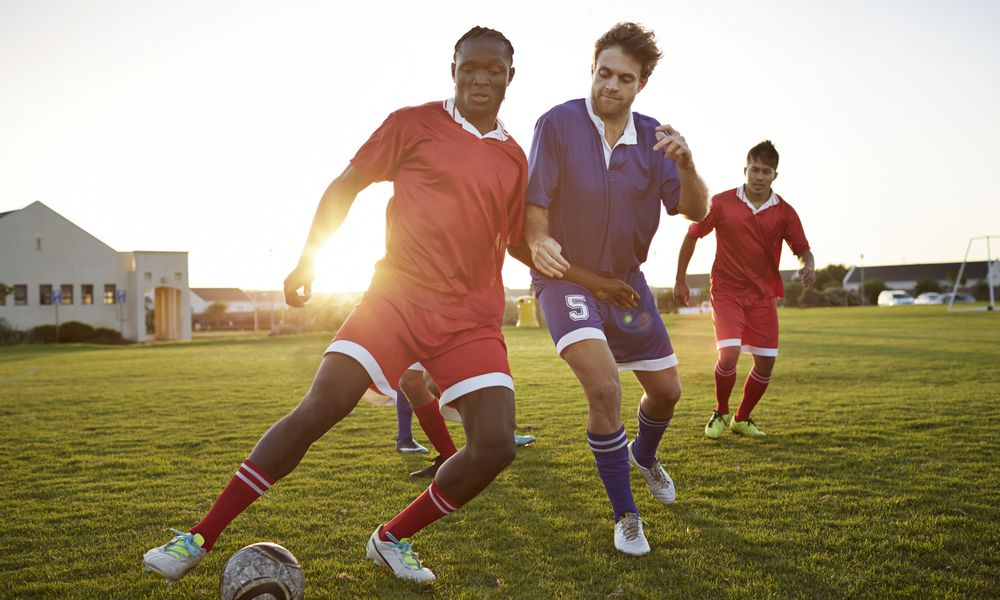 Soccer players battling to get the ball