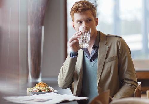 Man drinking water at restaurant
